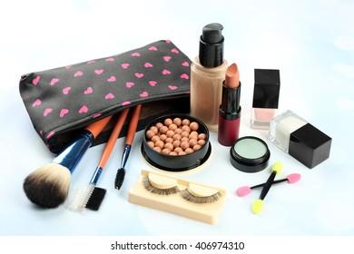 Makeup set with beautician, false eyelashes, brushes and cosmetics on blue background