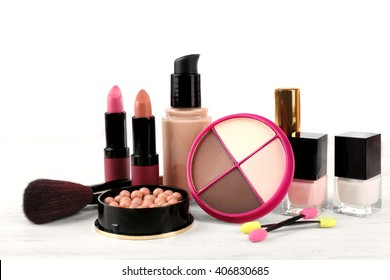 Makeup set with brush and cosmetics on light background