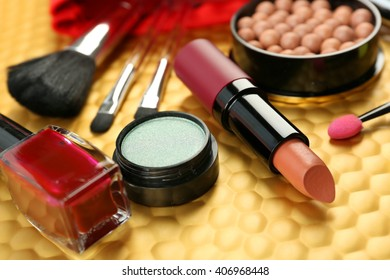 Makeup set with brushes and cosmetics on yellow background