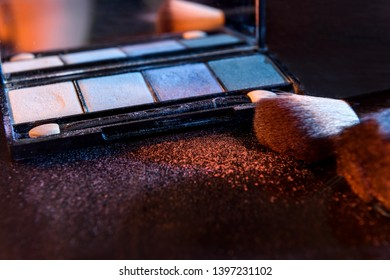 Makeup set with brushes and dust on dark background