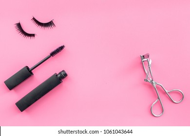 Makeup set for expressive eyelashes. Mascara, false eyelashes, eyelash curler on pink background top view space for text