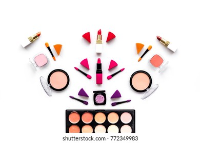 Makeup set pattern. Eyeshadows, rouge, nailpolish, lipstick, applicators on white background top view