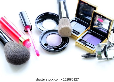 makeup set (shadows, lipstick, brush) on a white background