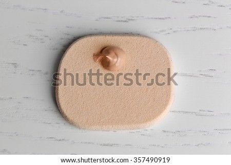 Makeup sponge with liquid foundation on wooden background