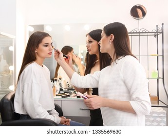 Makeup teacher with her student girl. Make up tutorial lesson at beauty school. Make up artist work in her studio. Portrait of visagist applying makeup on the eyebrow. Master class