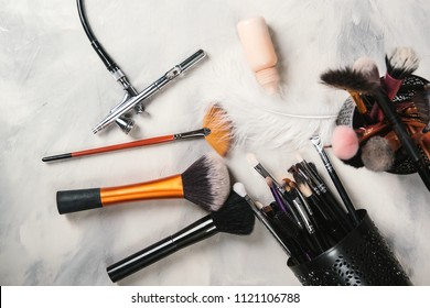 Makeup tools for professional makeup artist. Makeup brushes. Airbrush and jar of paint. Makeup tools and accessory on concrete gray background. Fashion and beauty concept.