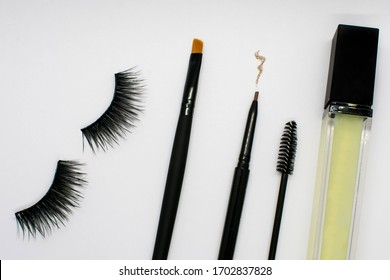Makeup tools, strip eyelashes and products against a white background