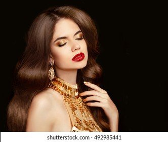 Makeup. Wavy hair. Beautiful brunette girl with long shiny healthy hairstyle. Fashion gold jewelry.  Red lips. Elegant lady in golden necklace isolated on black background.