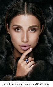 Makeup. Woman With Beauty Face On Black Background. Sexy Young Female Model With Professional Make-up In Luxury Black Fur And Expensive Gold Diamond Ring. Luxury Women Face Makeup. High Quality Image.