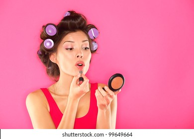 Makeup woman putting lipstick wearing hair rollers getting ready for going out. Funny image of beautiful pretty multiracial girl in pink dress on pink background.