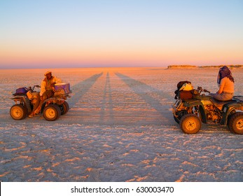 MAKGADIKGADI, BOTSWANA - AUGUST 29;Tourist and guide in glow of setting sun on quad bikes stop on scenic large flat area of salt pan desert  to take in view, August 29, 2007, Makgadikgadi Botswana