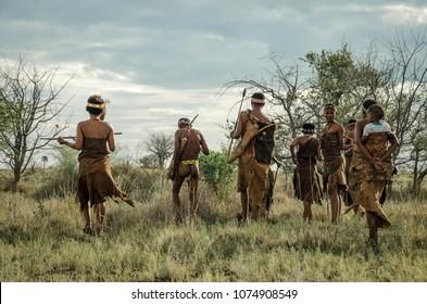 Makgadikgadi Salt Pans, Botswana - April 1st 2015: A group of Basarwa hunter/gatherers depart together on a foraging expedition.