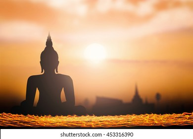 Makha Bucha day concept: Long exposure of candle light with silhouette Budha and  blurred tourist attraction in thailand on golden night background.