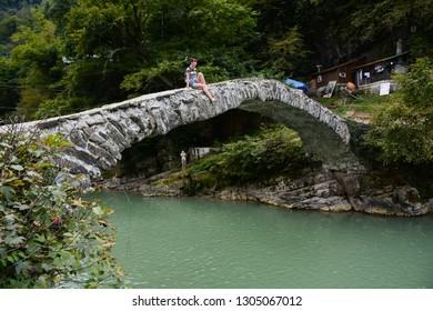 Makhuntseti, Georgia - September 20, 2018: Tourist girl sitting on Makhuntseti Arched Bridge near Makhuntseti Waterfall located in Adjara in Georgia