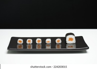 Maki sushi arranged on plate, one piece larger than the rest