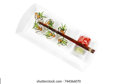 Maki Sushi - California Roll made of Raw Salmon, Cream Cheese and Deep Fried Vegetables inside. With wasabi and ginger. isolated over white background