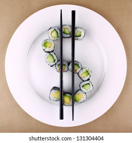 Maki sushi as dollar sign on white plate, top view