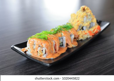 Maki sushi roll made of salmon top with wakame seaweed and special sushi top with crispy tempura flour, mayonnaise and flying fish roe - Japanese fusion