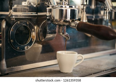 Making all kinds of coffee beverages. Brewing coffee with espresso machine. Making espresso with portafilter. Coffee cup. Small cup to serve hot coffee drink. Espresso being brewed in coffeehouse.