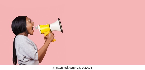Making announcement. Black woman shouting in megaphone towards copy space over pink background, panorama