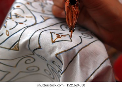 making batik using canting on a cotton cloth