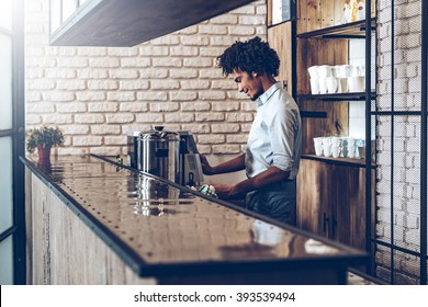 Making best coffee. Side view of young African man using coffee machine with smile while standing at bar counter