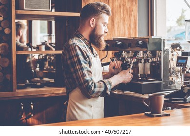 Making best coffee in this city. Side view of young bearded man in apron making coffee while standing at cafe