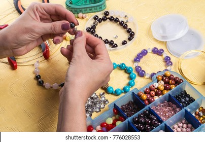 Making bracelet of colorful beads.