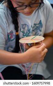 Making a braided friendship bracelet using a cardboard and yarn.