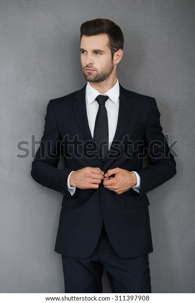 Making business looking good. Confident young businessman adjusting his jacket and looking away while standing against grey background