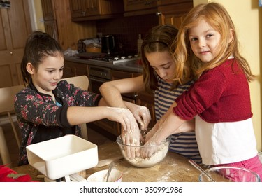Making the Butter and Flour Rub. Three sisters are working through a recipe for making gingerbread. Here they are rubbing the flour and butter together by hand. They are enjoying the messy work.