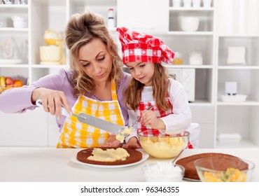 Making a cake together - woman and little girl in the kitchen
