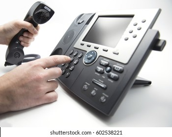 Making a call, man is dialing IP telephone keypad