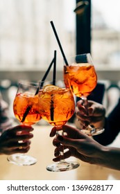 Making a celebratory toast with aperol spritz cocktails. Friends toasting with summer cocktails