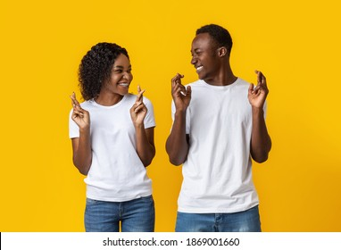 Making cherished wish. Young cheerful african-american couple with crossed fingers looking at each other and smiling, yellow studio background. Emotional black man and woman praying for good
