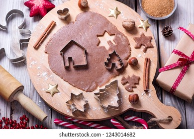 Making christmas cookies, baking gingerbread cookies, raw dough and cutters on wooden background