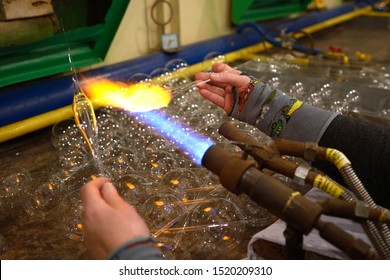 Making Christmas decorations. Glassblower's hand warming glass blank with a gas burner