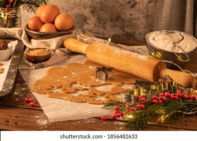 Weihnachten pflücken gebackene Kekse. Roher Teig in Form von Lebkuchen Mann, Weihnachtsbaum, Stern, Schneeflocken auf Papier auf Tablett auf rustikalen Tisch mit rollendem Pin. Backvorbereitung