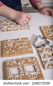 Making of christmas gingerbread house. Walls decorating. cooking, people, christmas and decoration concept, woman making gingerbread houses at home