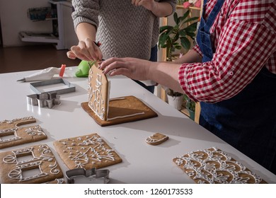 Making of christmas gingerbread house. Walls binding. cooking, people, christmas and decoration concept, woman making gingerbread houses at home
