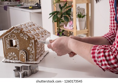 Making of christmas gingerbread house. Walls decorating. cooking, people, christmas and decoration concept,  happy woman making gingerbread houses at home