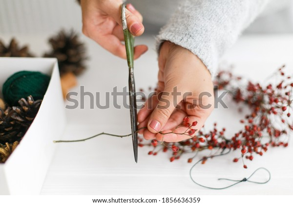 Making christmas wreath on white wooden table, holiday advent. Female hands making simple christmas wreath with red berries on white wooden table. Festive workshop