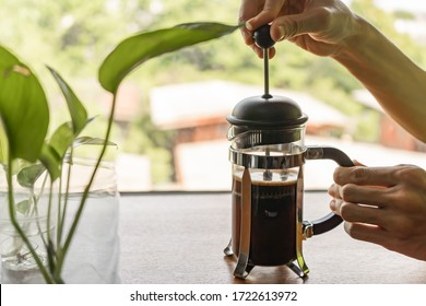 Making coffee with French Press coffee maker. Pressing the plunger of the French press coffee maker down.