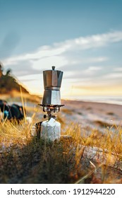 Making coffee outdoors on gas camping fire during beautiful sunset by the beach