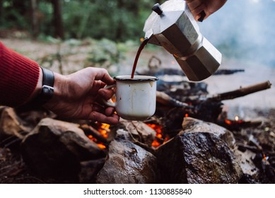 Making coffee process on the campfire. Man pour coffee in potter cup