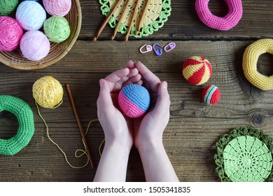 Making colored crochet balls. Toy for babies and toddlers to learn mechanical skills and colors. On the table threads, needles, hook, cotton yarn. Handmade crafts. DIY concept.