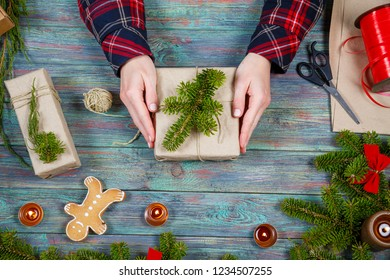 Making craft creative gift boxes, woman decorating Christmas presents with natural decorations, top view