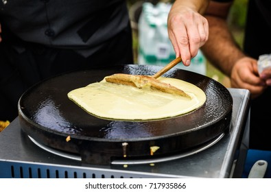 Making of crepes pancakes in open market festival fair. A hand is making crepes outdoors on a metal griddle with wooden stick on a outdoor summer fest.