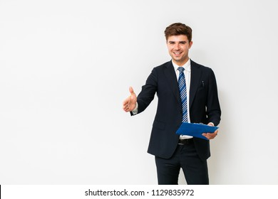 making a deal. Handsome elegant man in suit, businessman or salesman, stretches his hand to conclude a business with contract in hands