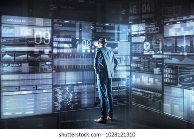 Making decision. Calm concentrated young programmer with virtual reality glasses standing in front of a giant transparent screen and thoughtfully looking at it while making important decision